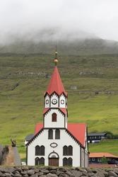 Sandavágur (Sandy Bay) Church with its distinctive bright red roof, Vagar Island, Faroe Islands.