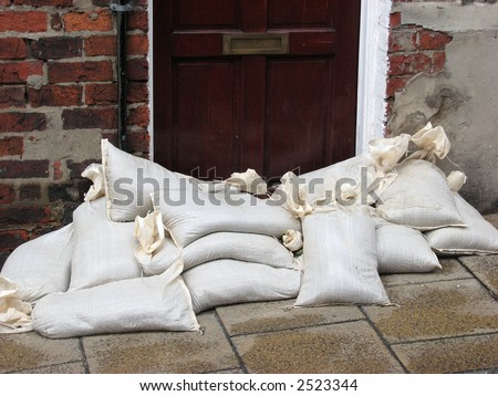 Sandbags stacked in front of door acting as a flood barrier. York, North Yorkshire, UK