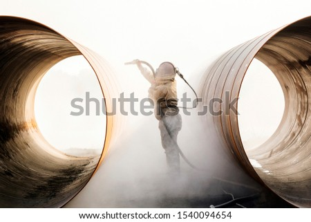Photo of  Sandblasting or abresive blasting for steel pipes before painting and coating.