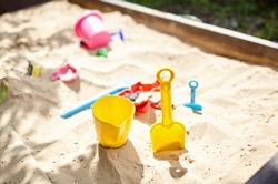 Sandbox outdoor. Children's wooden sandbox with various toys for the game. Summer concept. Selective focus with shallow depth of field