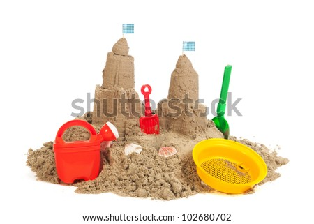 sandcastle at the beach with plastic toys isolated over white background