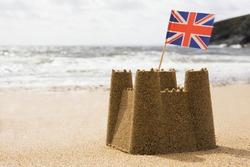 Sandcastle On Empty British Beach With UK Union Jack Flag Flying