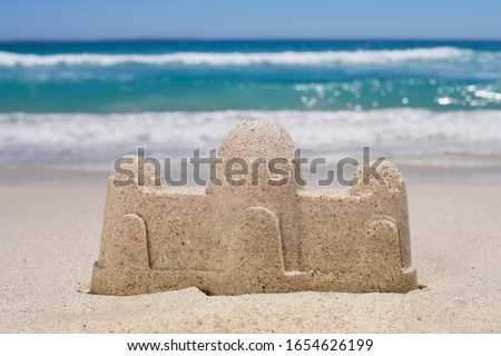 Sandcastle on sandy beach, sea in background