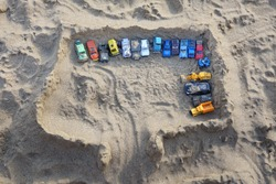 Sandcastle Top View On Sea Beach With Kids Toys. Sand Castle Or Fort With Many Colorful Plastic Car On Summer Sea Coast Overhead View. Abstract Background.