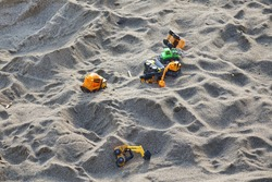 Sandcastle With Kids Toys. Sand Castle Or Fort With Many Colorful Plastic Car On Summer Sea Coast Overhead View. Abstract Background.