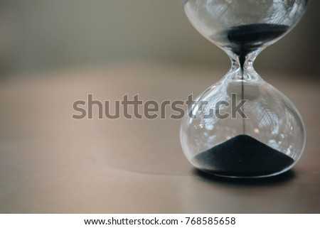 Sandglass, hourglass or egg timer on wooden floor showing the last second or last minute or time out. With copy space.