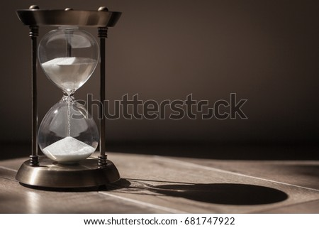 Sandglass, hourglass or egg timer with shadow showing the last second or last minute or time out. With copy space. Time management.  #681747922