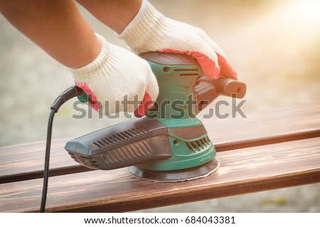 Sanding a wood with orbital sander outdoor