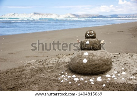 Sandman-snowman with the shell buttons on the beach
