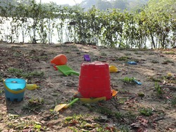 sandpit next to the lake with red bucket and many plastic toys design for leisure activity outdoor