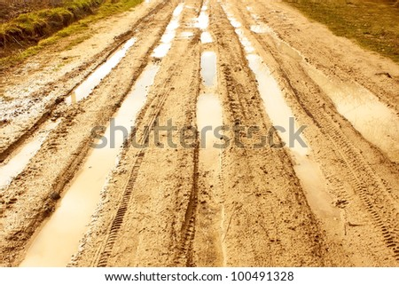 Sandstone covered rural road after the rain with wheels traces filled with water