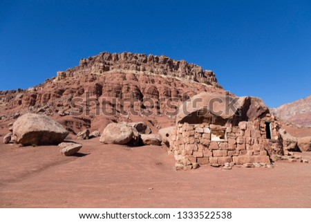 Sandstone house in ruins, boulders and mountain in Cliff Dwellers, on northern Arizona's Vermillion Cliffs Scenic Drive near Kaibab during a sunny morning