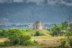 Sandstone St. Nicholas church with Dinaric Alps in background, is Roman Catholic church in early Romanesque architecture from 11th century, located between Zaton and Nin in Croatia