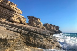 Sandstone yellow stratum rocks on coastline with crashing waves of stormy sea. Landscape.