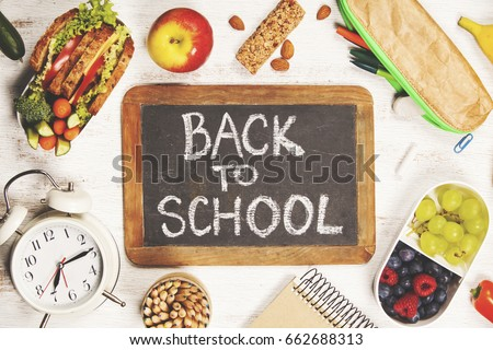 Sandwich, apple, grape, carrot, berry in plastic lunch boxes, stationery and bottle of water on white background. Back to school concept.
