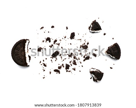 Sandwich chocolate cookies with a sweet cream with crumbs isolated on white background.