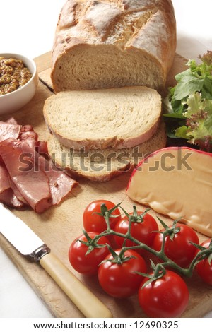 Sandwich ingredients - loaf of sourdough bread, lettuce, tomatoes, pastrami, edam cheese, and seeded mustard.
