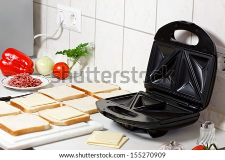Sandwich maker, toasts and vegetables on the table. Stock photo ©