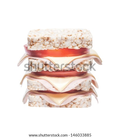 sandwich of corn crackers with ham, cheese and tomato