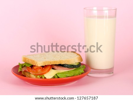 Sandwich on plate with milk on pink background