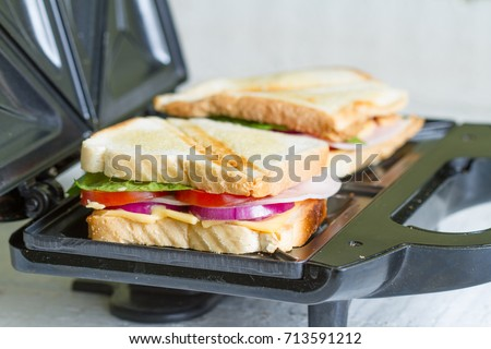 Sandwich toaster with toast and ingredients Stock photo ©