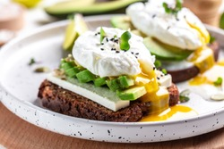 Sandwich with avocado and poached egg. Healthy nutritious paleo keto breakfast concept.