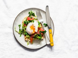 Sandwich with avocado, green salad, smoked salmon and poached egg on a light background, top view. Delicious healthy nutritious breakfast, brunch