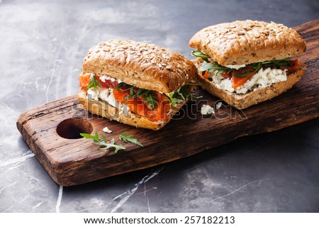 Sandwich with cereals bread and salmon on dark marble background