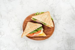 Sandwich with cheese, sausage, tomatoes and herbs on a wooden plate