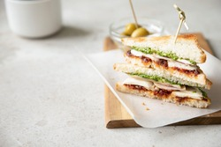 Sandwich with chicken breast, dried tomatoes, mozzarella and pesto with olives on background.