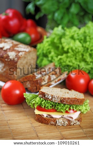 Sandwich with chicken brest, swiss cheese, lettuce and tomato on brown bread.