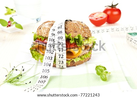 Sandwich with fresh vegetables and cheese and measuring tape wrapped around it on table with fresh herbs.