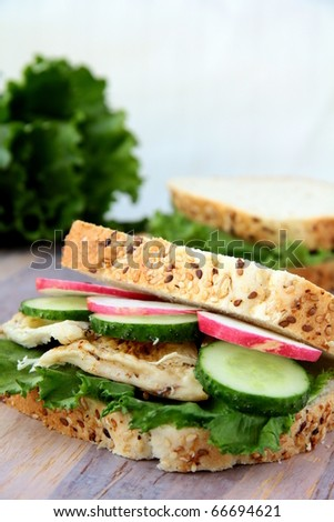 sandwich with fresh vegetables and chicken on a wooden board