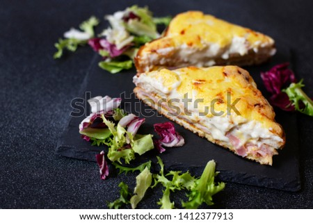 Sandwich with ham, cheese and bechamel sauce. A traditional french croque-monsieur sandwich served with lettuce leaves on a black plate. Black background. Close-up. Space for text Photo stock ©