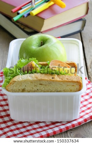 sandwich with ham, green salad and apple in a box - school lunch