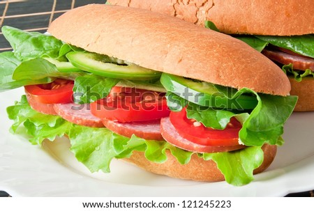 Sandwich with ham, tomato, cucumber and arugula on the white plate