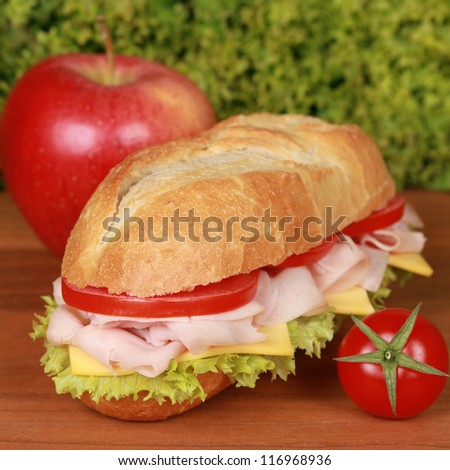 Sandwich with ham, tomatoes, lettuce and cheese served with an apple