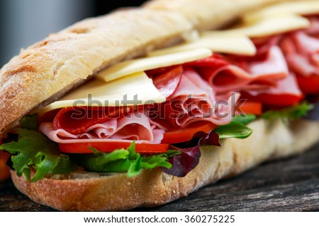 Sandwich with lettuce, slices of fresh tomatoes, salami, hum and cheese