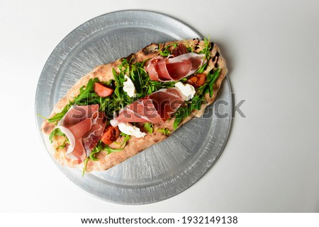 Sandwich with prosciutto, cheese and fresh arugula served on a metal tray over white background. Italian cuisine concept. Foto stock ©
