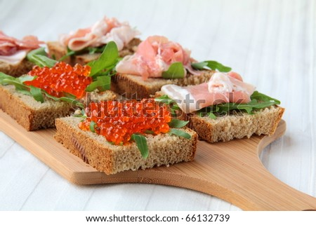sandwich with red caviar and arugula on a wooden board
