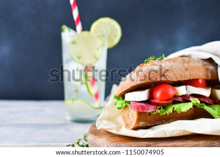 sandwich  with salami, brie cheese, lettuce and cherry tomatoes on a wooden plate, a glass of lemonade with lime, ice and thyme. selective focus and copy space
