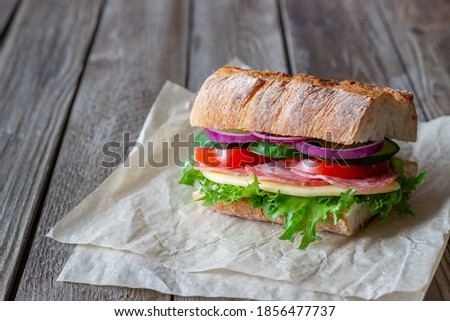 Sandwich with sausage, cheese, green salad, tomatoes, cucumbers and onions. Fast food. Breakfast. Healthy eating Stok fotoğraf ©
