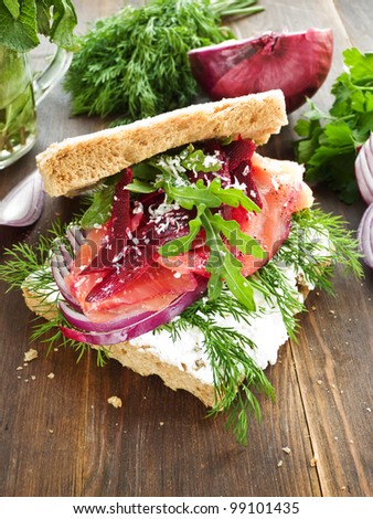 Sandwich with smoked salmon, cottage cheese and herbs. Shallow dof.