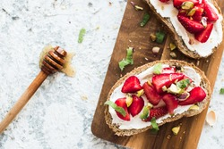 Sandwich with strawberries, soft cheese, pistachios, mint and honey on wooden board on grey background. Top view.