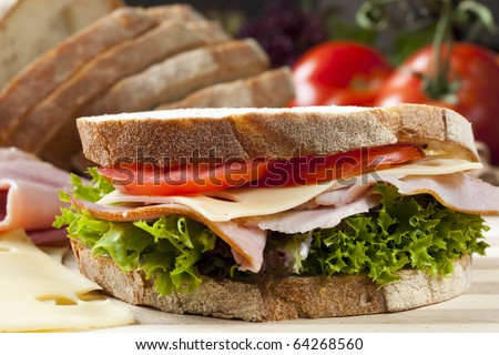 Sandwich with Swiss cheese, ham, tomato and curly lettuce, on crusty fresh-sliced bread.