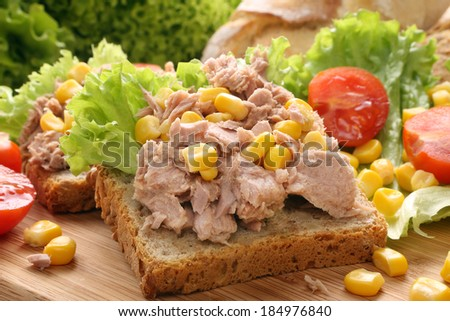 Sandwich with tuna corn and tomato on wood