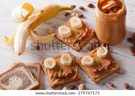 Sandwiches for children with peanut butter and banana on the table. horizontal view from above