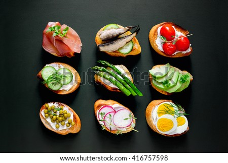 Shutterstock Sandwiches on a dark background, or assorted canapes, top view