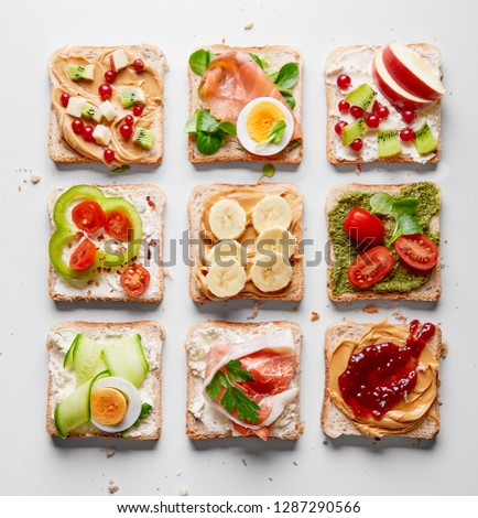 Sandwiches variation with vegetables, fruits, meat, eggs and sweets viewed from above. Variety of bruchetta breads arranged for a tasty and healthy breakfast. Top view