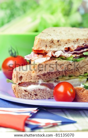 Sandwiches with bacon, chicken, lettuce and tomato with malted bread, close-up shot